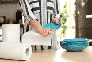 woman cleaning off blue glass plates with paper towls