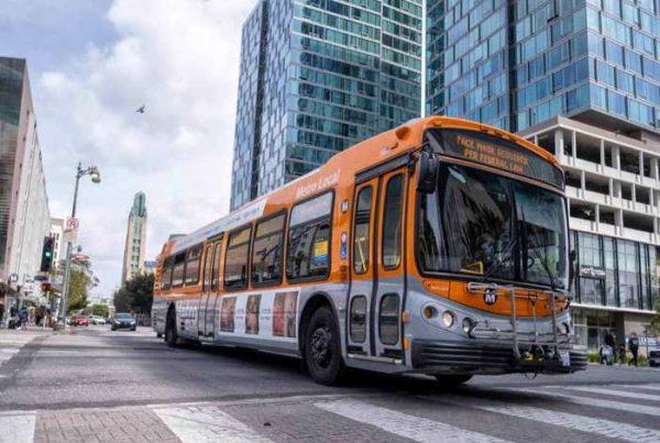Orange metro bus driving on busy street